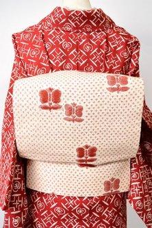 アイボリーとブリックルージュの十字絣と遠州椿愛らしい正絹紬京袋帯